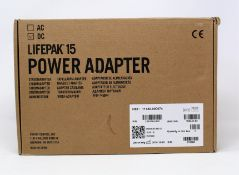 A boxed as new Physio-Control LIFEPAK 15 DC Power Adapter (P/N: 11140-000074) (Box opened, some