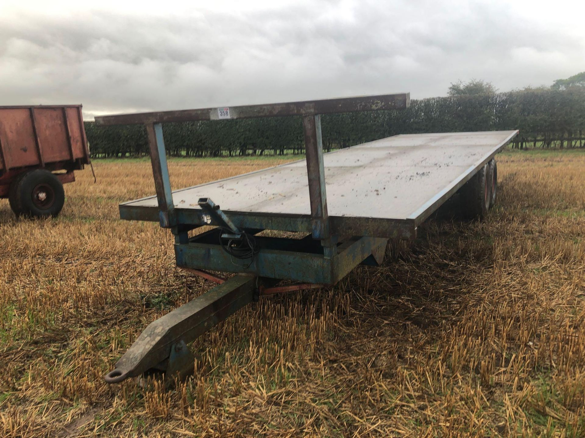 Scalin twin axle 28ft flat bed trailer with wooden floor.