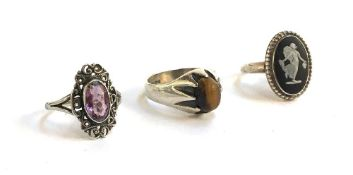 Three silver dress rings, one set with Tigers Eye, another an amethyst and the third small cameo