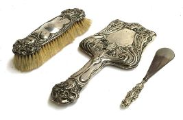 An Early 20th century chased silver hand mirror, with bevelled shaped plate; together with clothes