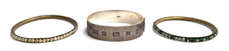 A silver hinged bracelet marked Birmingham 1977, BLtd, with two other bangles