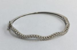 18ct white gold and diamond bracelet in the form of a hinged bangle. One side is set with approx.