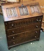 A 20th century oak bureau, linen fold decoration, fall front over four graduating drawers,