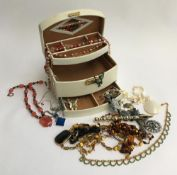 Cream jewellery box containing various bead necklaces and others