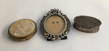 A small silver dressing table pot; enamel and glass set oval picture frame; and a compact (3)