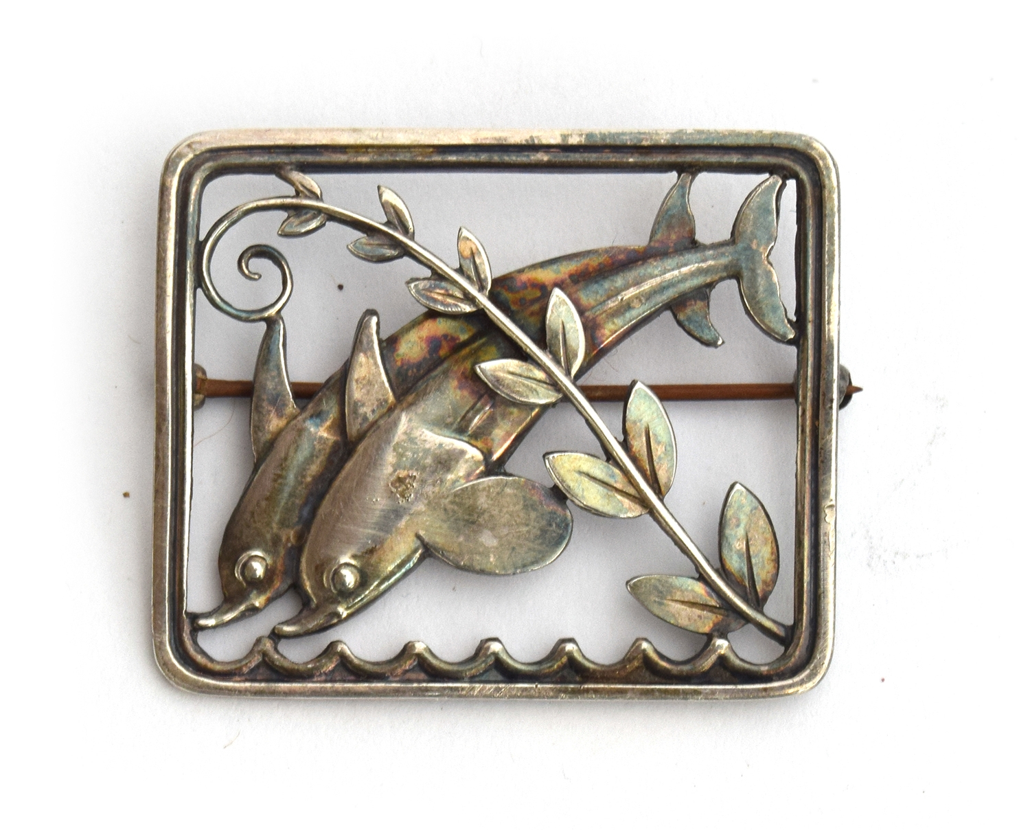 A c.1940s Georg Jensen sterling silver brooch featuring two dolphins designed by Arno Malinowski,