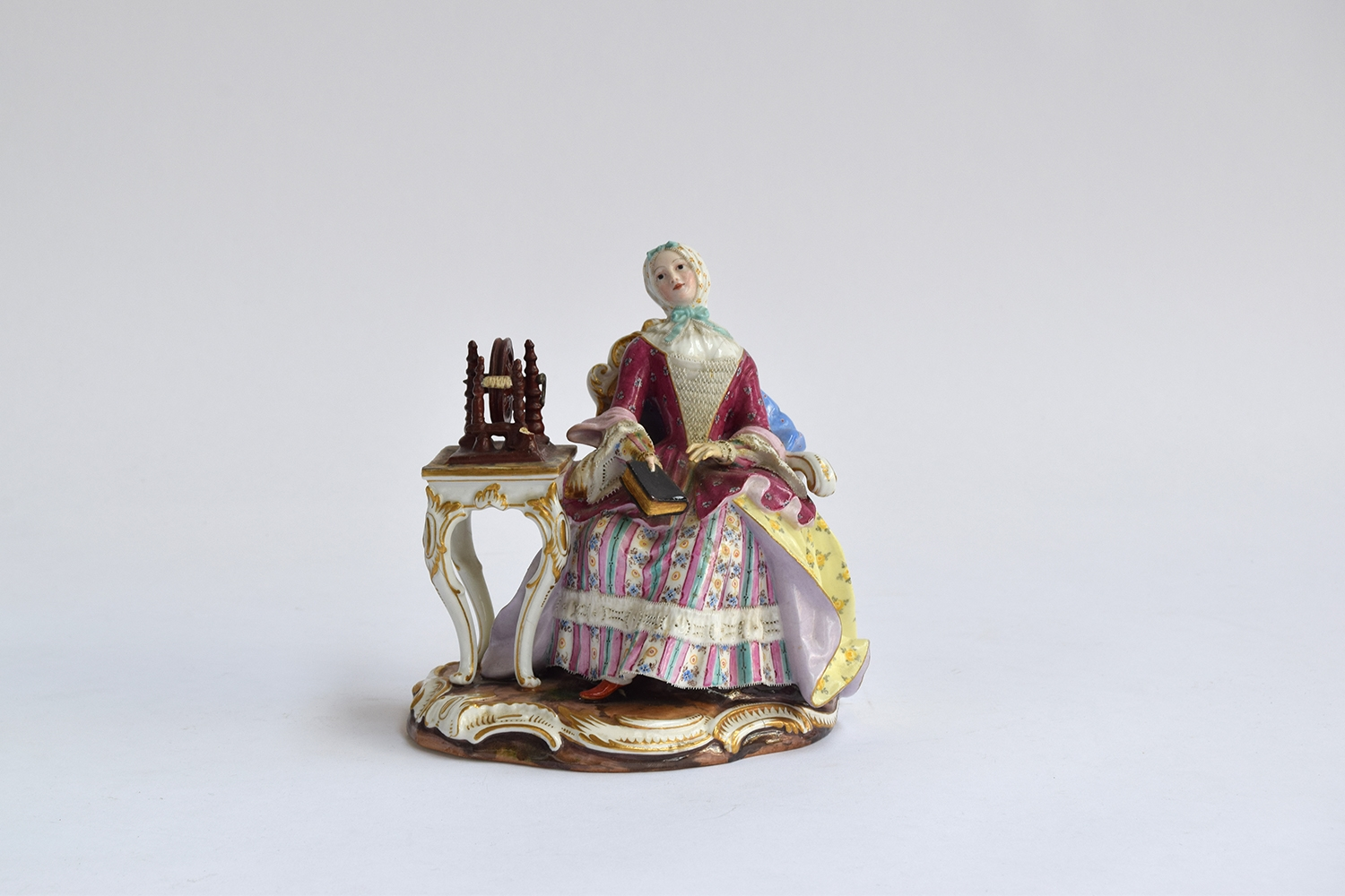 A 19th century Meissen group of a seated lady at a spinning wheel, 'The Good Housekeeper' or '