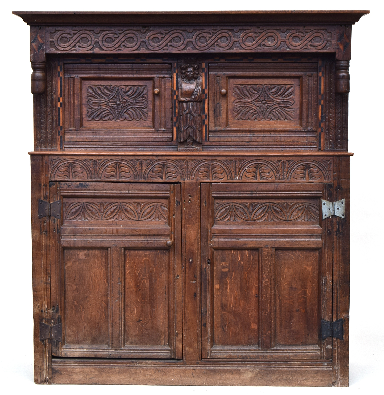 A 17th century joined oak court cupboard, boarded top, the upper section with turned pendants and