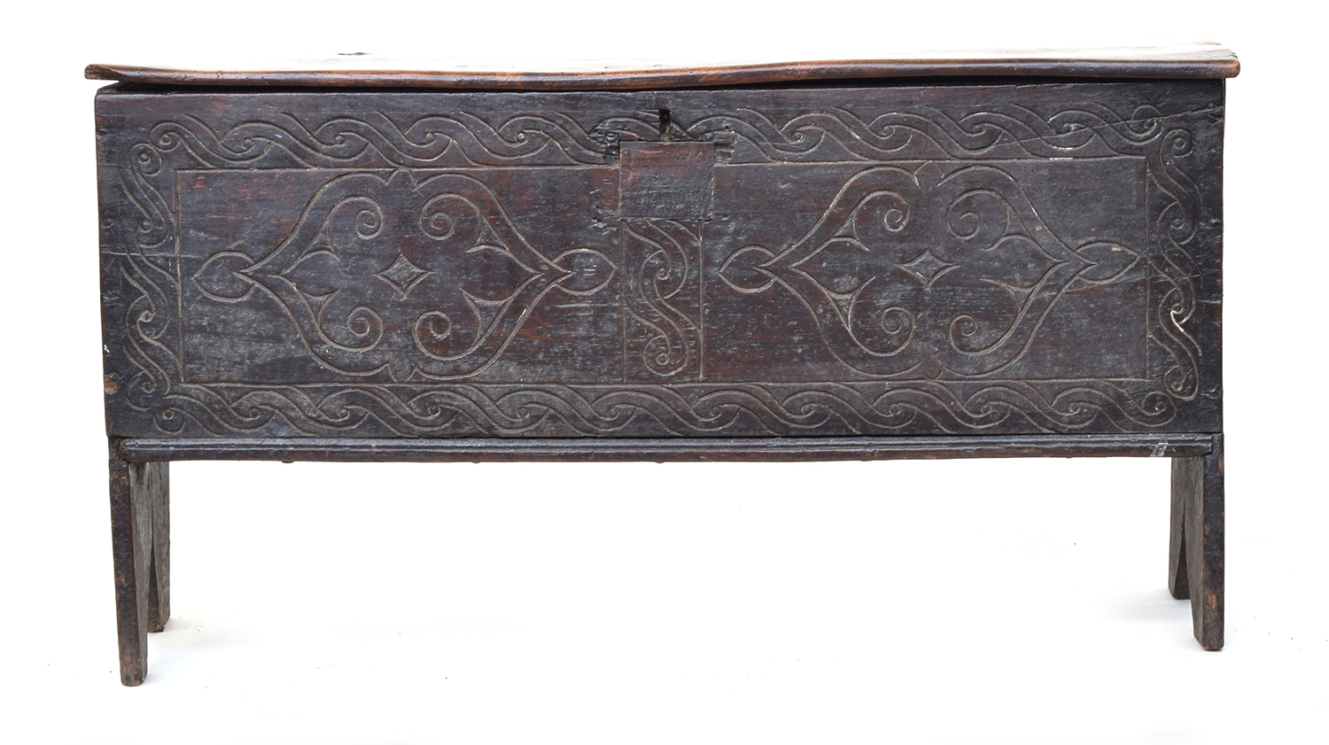 A 17th century vernacular six plank elm and oak coffer, with cut-in feet to the end boards, 103cm