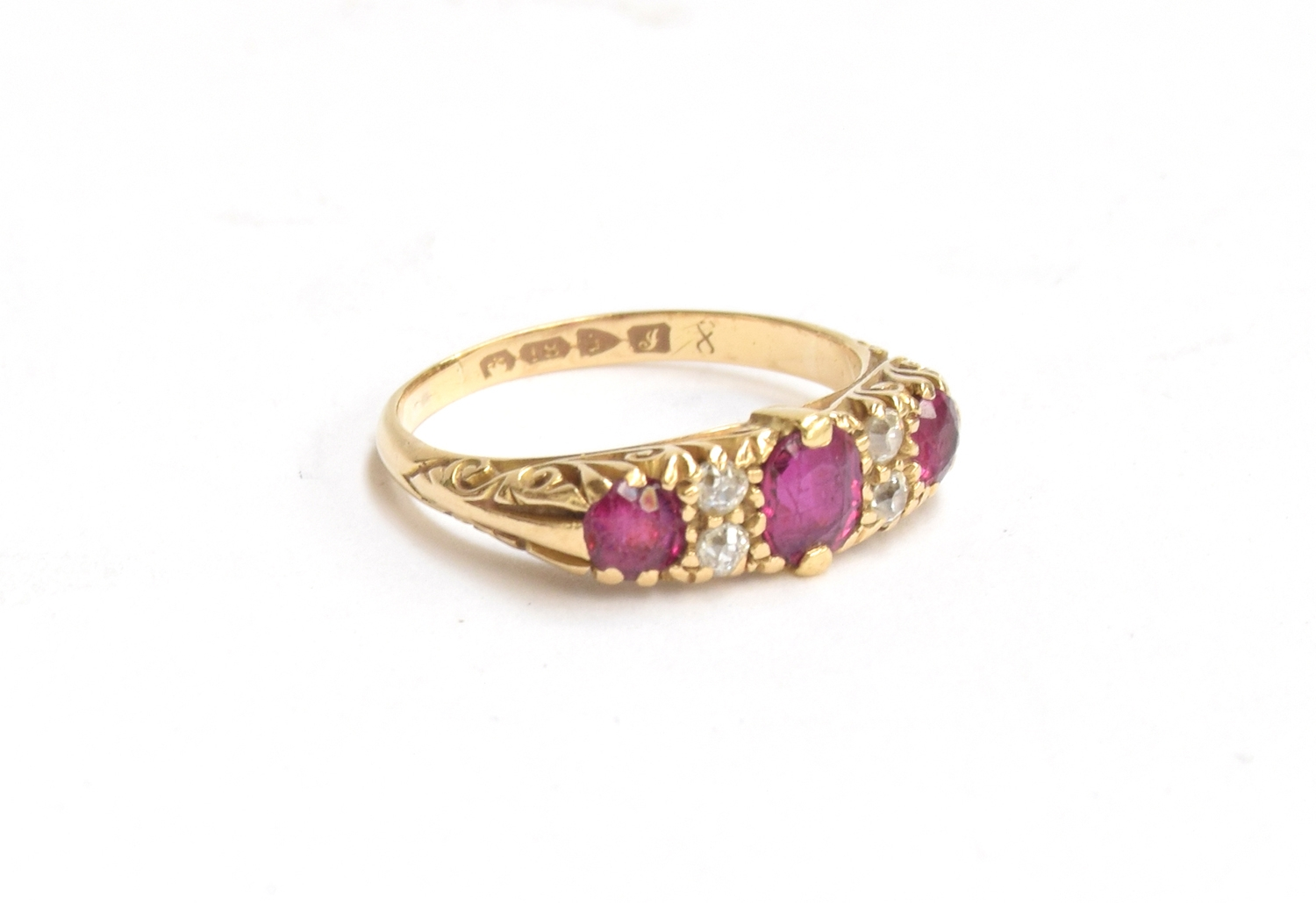 An 18ct gold dress ring set with 3 rubies and 4 small diamonds on a decorated shank, gross weight