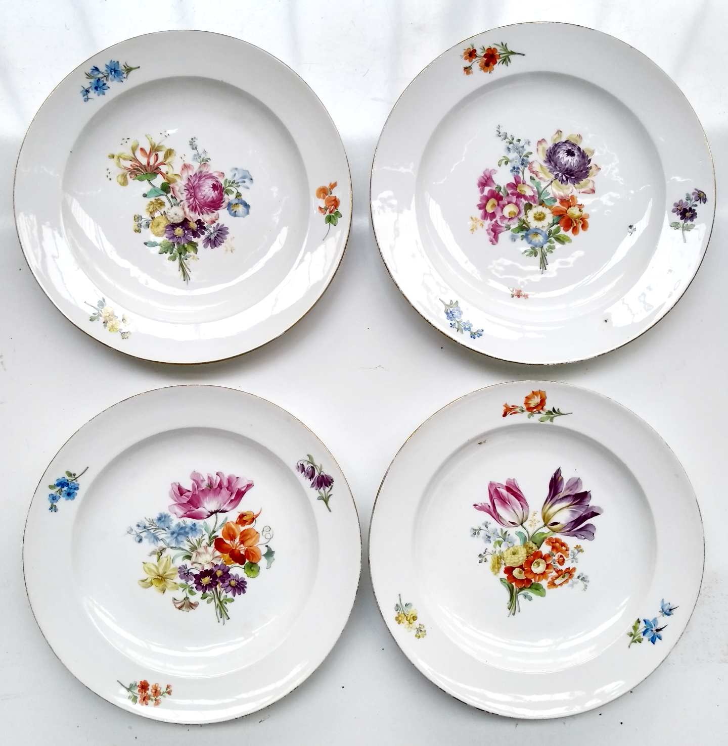 Four late 18th century Meissen hand painted floral plates, blue crossed sword marks to base, rim
