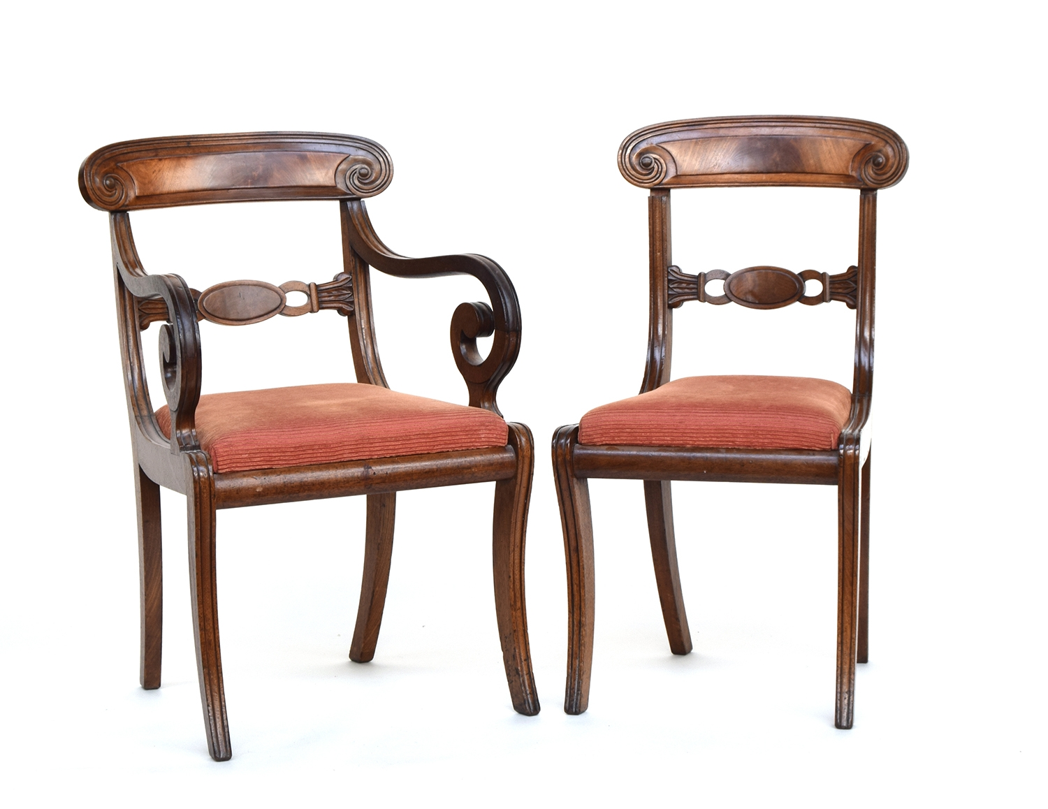 A set of seven Regency mahogany dining chairs with scroll carved rails, drop in seats, on sabre legs