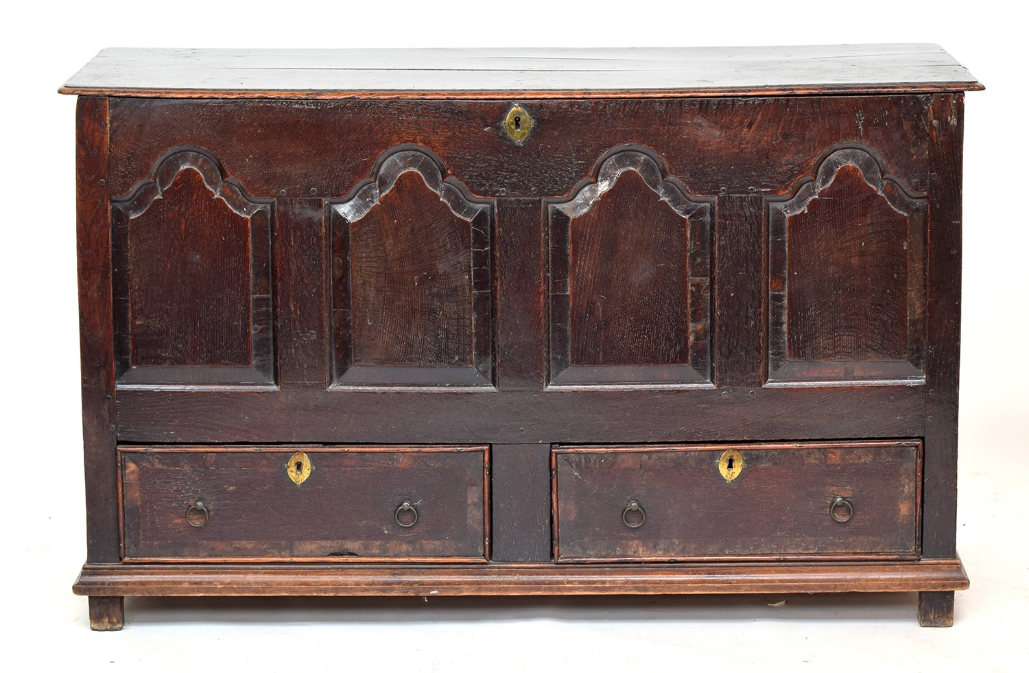 A George III four panel oak mule chest, hinged top over four shaped fielded panels, above two