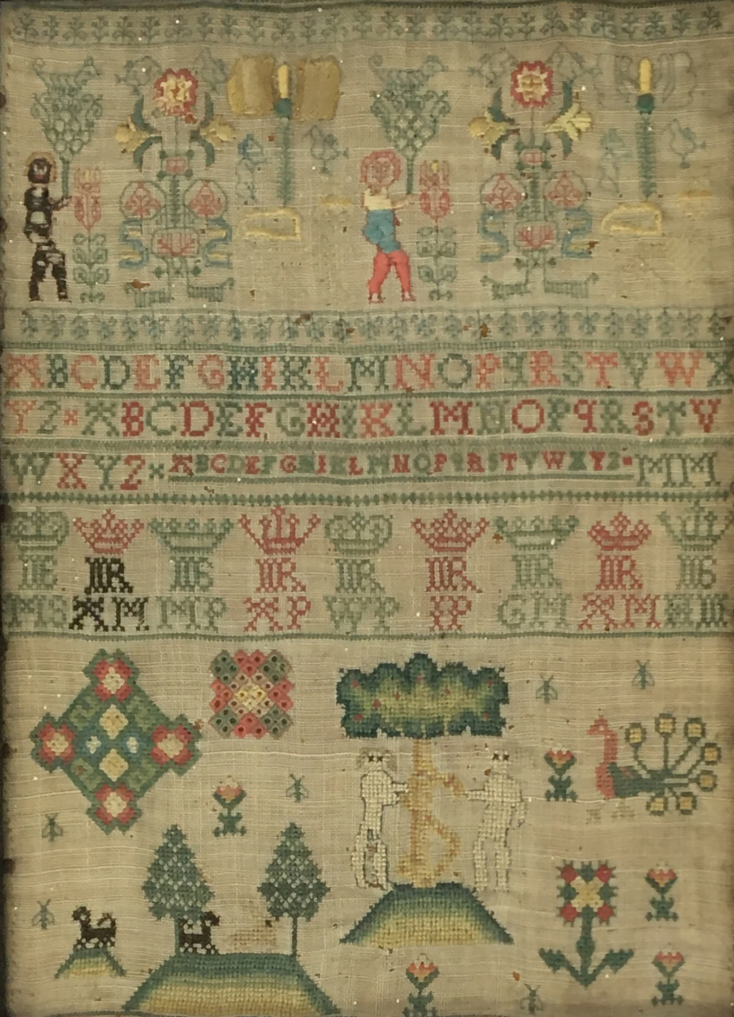 An early alphabet sampler, also worked with trees, animals, and figures, 30.5 x 22cm