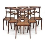 A set of six Regency dining chairs, the crest rails with scroll carving, the carved horizontal