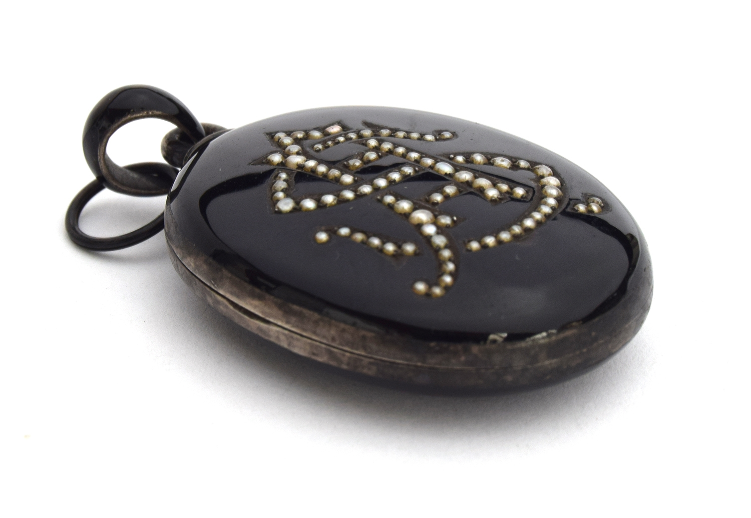 Victorian silver and black enamel mourning locket with the initials 'SA' formed in seed pearls, 5cmH