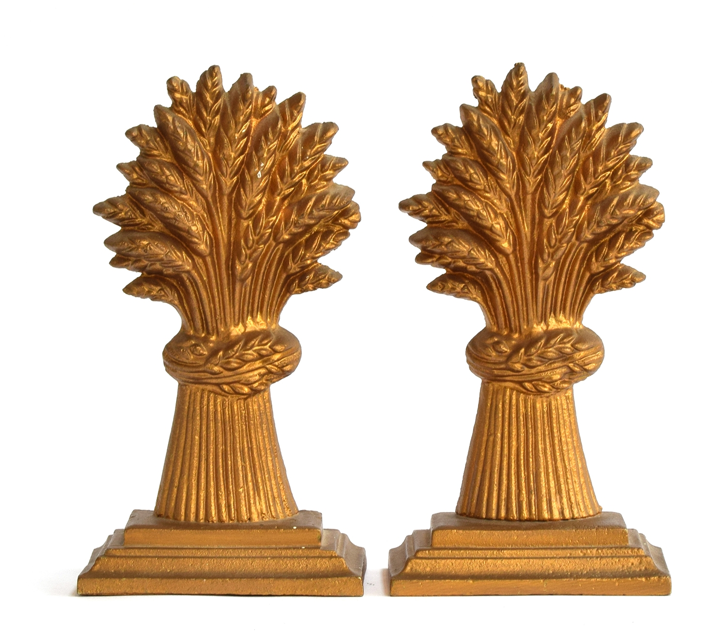 A pair of brass door stops in the form of wheat sheaves on stepped plinth bases, heightened in gilt,