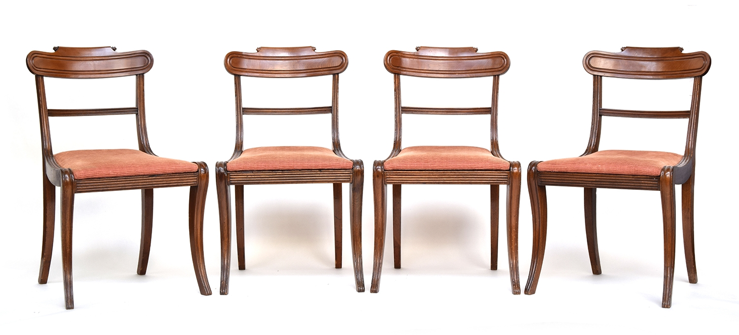 A set of four Regency mahogany dining chairs, curved rail over drop in seats, on swept legs
