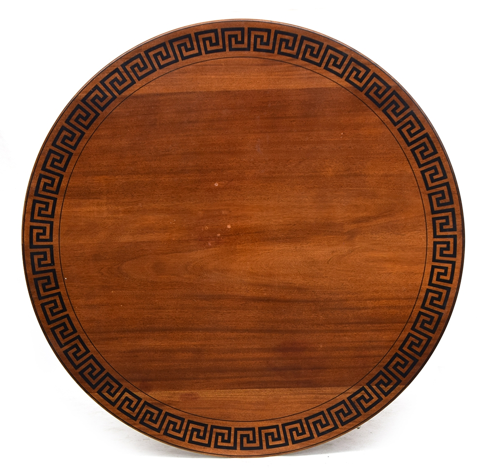 A late 19th/early 20th century circular dining table, decorated with ebonised Greek key frieze, on