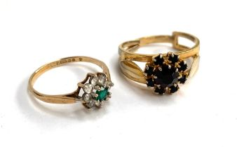 A 9ct ring set with central green stone surrounded by eight white stones in the form of a flower;