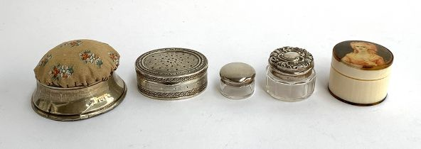 An 800 silver pill box; a silver hallmarked pin cushion; two silver topped glass pots; and a bone