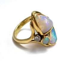An 18ct yellow gold ring set with freeform opals, and two brilliant cut diamonds (approx. 0.