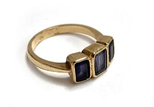 A 9ct gold ring set with three amethysts, size O, 3.6g