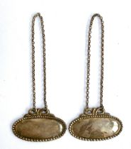 A pair of Tiffany & Co. vacant silver decanter labels