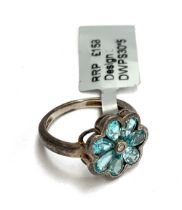 A sterling silver ring in the form of a flower, seven pear cut apatites surrounding a central