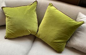 A pair of green velvet cushions, with purple piping, approx. 50cm2