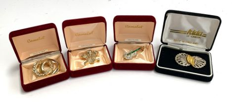 Three Camelot brooches, yellow metal set with faux diamonds, in the form of a fleur de lys,