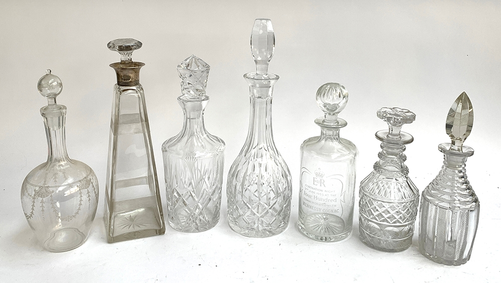 A lot of seven decanters, one of tapered square form, with silver collar by Maxfield & Sons,