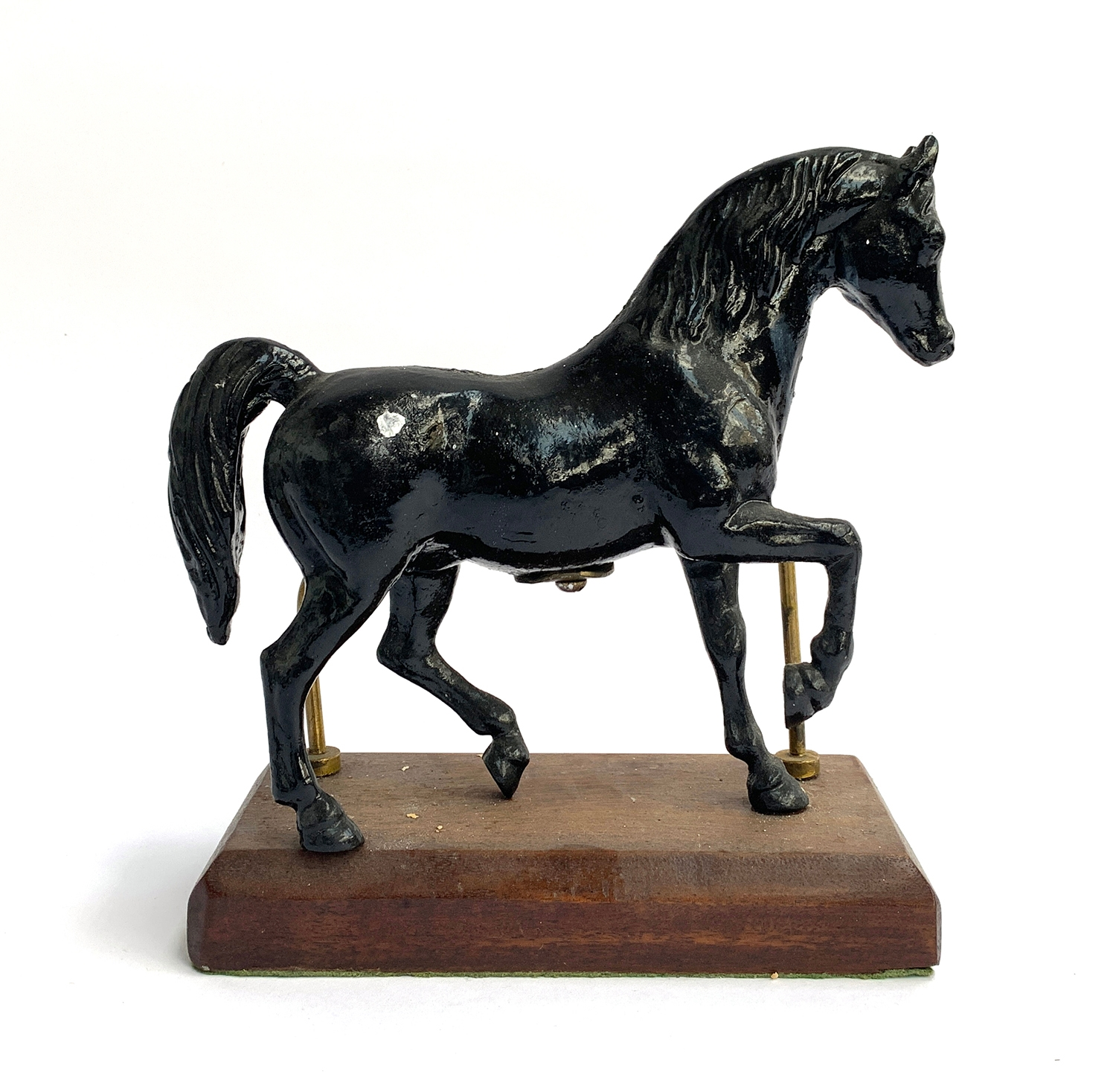 A painted figure of a horse, mounted on a wooden plinth, 26cm high