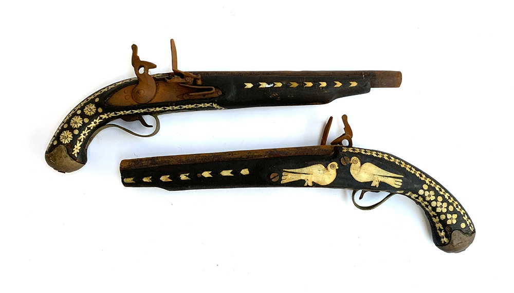 A pair of flintlock pistols, each with bone inlay