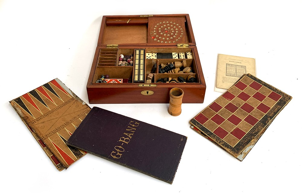 A 19th century mahogany cased compendium of games to include chess and backgammon boards and pieces;
