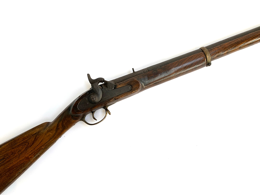 An antique percussion rifle, the side plate marked 'made in', the barrel stamped 389/85, length of
