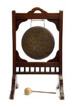 A Victorian Aesthetic movement oak and brass dinner gong, 92cm high, the brass drum 35cm diameter