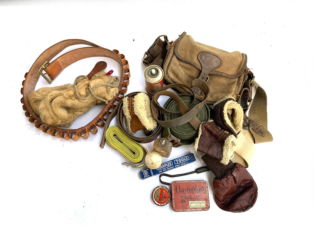 A mixed lot of items including a leather cartridge belt with brass buckle, wrist warmer, various