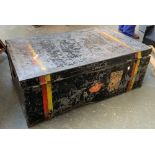 A metal travel trunk with hinged lid and travel stickers, double red and yellow stripe, 89x54x33cm