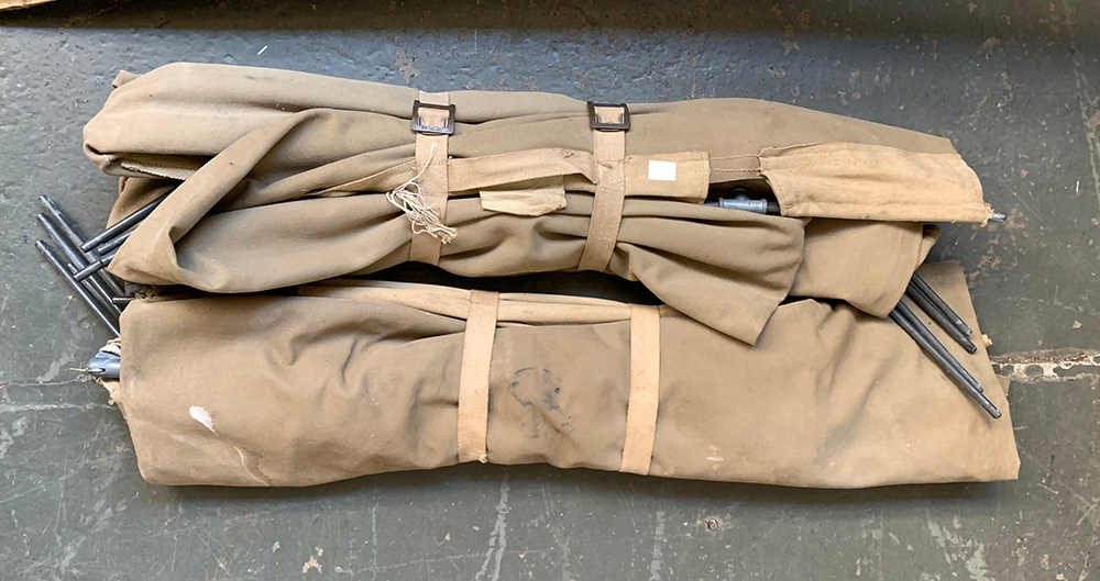 A pair of military issue collapsible canvas beds