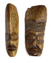 Two African carved bone masks, each approx. 28cm high