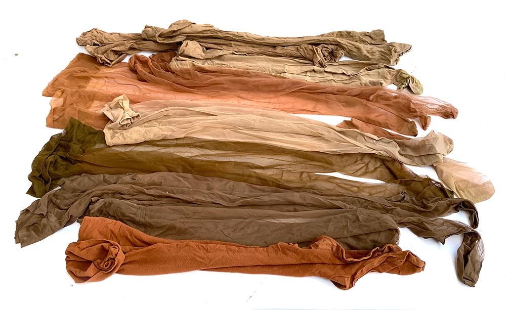 Nine pairs of vintage silk stockings, various shades