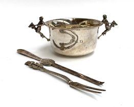 A silver tastevin, the twin handles in the form of jockeys astride hobby horses, Mappin & Webb,
