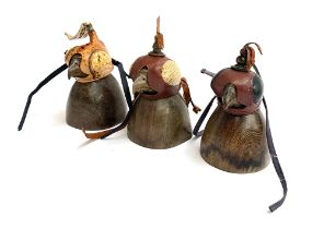 Three falconry hoods, on carved wooden stands (3)