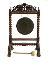 A Victorian oak and brass dinner gong, surmounted with pierced carved scrolls and a pair of mythical