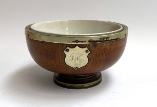 A ceramic lined wooden presentation bowl, with plated foot, rim, one vacant plaque, the other