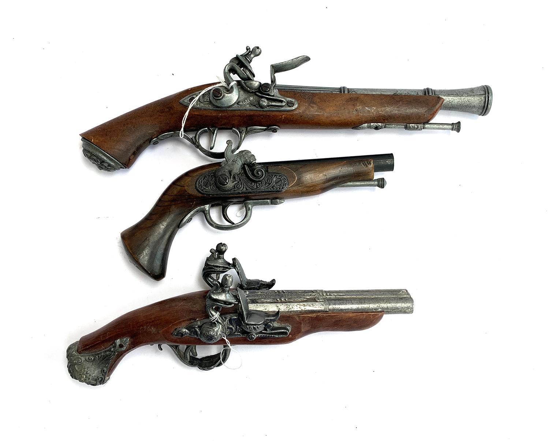 Three replica flintlock pistols, one with double barrel