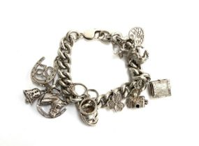 A hallmarked silver charm bracelet with ten charms, approx. 87g