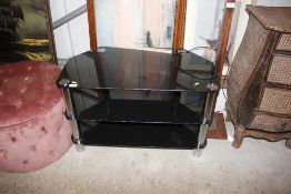 A black glass and metal mounted three tier television stand