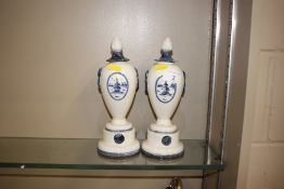 A pair of blue and white pottery vases and covers